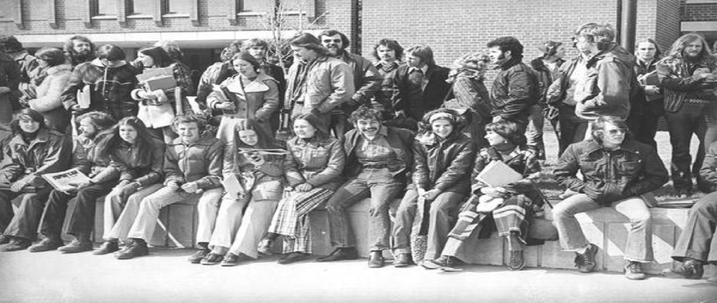 Students from Mankato State College sitting on wall in front of Armstrong Hall in the 1970s